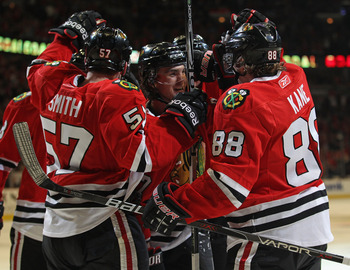 CHICAGO, IL - APRIL 10: Michael Frolik #67 of the Chicago Blackhawks (center) is congratulated by teammates including Ben Smith #57 and Patrick Kane #88 after scoring a goal in the 2nd period against the Detroit Red Wings at the United Center on April 10,