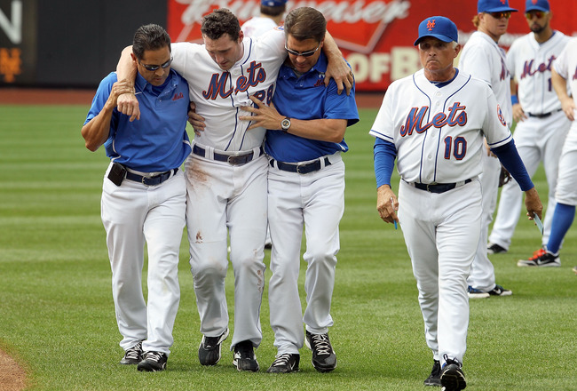 NEW YORK, NY - AUGUST 07:  Daniel Murphy #28 of the New York Mets is helped off the field by head trainer Ray Ramirez (L), trainer Mike Herbst and manager Terry Collins #10 after a seventh inning injury trying to prevent a stolen base against the Atlanta