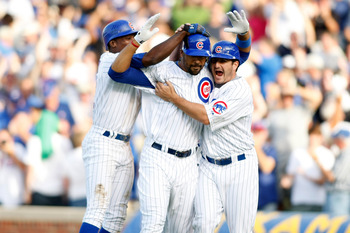 CHICAGO, IL - SEPTEMBER 18: Jason Marquis #21 and Alfonso Soriano #12 of the Chicago Cubs celebrate with Derrek Lee #25 after he drove in the game winning run against the Milwaukee Brewers at the Wrigley Field on September 18, 2008 in Chicago, Illinois. T