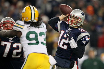 FOXBORO, MA - DECEMBER 19:  Quarterback Tom Brady #12 of the New England Patriots throws a touchdown pass to tight end Aaron Hernandez #85 (not pictured) in the fourth quarter of the game against the Green Bay Packers at Gillette Stadium on December 19, 2