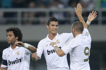 TIANJIN, CHINA - AUGUST 06:  Karim Benzema (Right) celebrates a goal with Cristiano Ronaldo (Center) of Real Madrid during the pre-season friendly match between Tianjin Teda and Real Madrid at Water Drop Stadium on August 6, 2011 in Tianjin, China.  (Phot