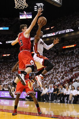 MIAMI, FL - MAY 22:  Dwyane Wade #3 of the Miami Heat drives for a shot attempt against Omer Asik #3 of the Chicago Bulls in Game Three of the Eastern Conference Finals during the 2011 NBA Playoffs on May 22, 2011 at American Airlines Arena in Miami, Flor