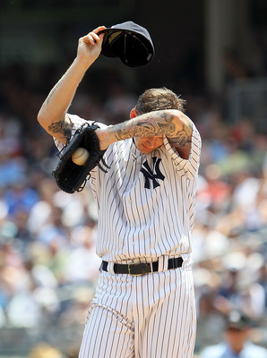 NEW YORK, NY - JULY 23:  A.J. Burnett #34 of the New York Yankees wipes away sweat during the first inning against the Oakland Athletics on July 23, 2011 at Yankee Stadium in the Bronx borough of New York City.  (Photo by Jim McIsaac/Getty Images)