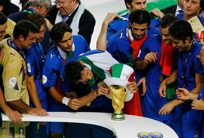 BERLIN - JULY 09:  Marco Materazzi of Italy places an Italian hat on the World Cup trophy following victory in a penalty shootout at the end of the FIFA World Cup Germany 2006 Final match between Italy and France at the Olympic Stadium on July 9, 2006 in