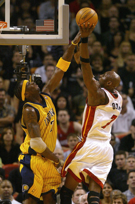 MIAMI - MAY 18:  Jermaine O'Neal #7 of the Indiana Pacers contests a shot by Lamar Odom #7 of the Miami Heat during first half action in game 6 of the Eastern Conference Semifinals during the 2004 NBA Playoffs May 18, 2004 at the American Airlines Arena i