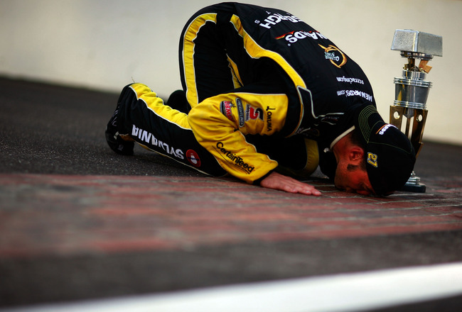 INDIANAPOLIS, IN - JULY 31:  Paul Menard, driver of the #27 NIBCO/Menards Chevrolet, poses as he kisses the bricks after winning the NASCAR Sprint Cup Series Brickyard 400 at Indianapolis Motor Speedway on July 31, 2011 in Indianapolis, Indiana.  (Photo b