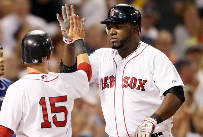 BOSTON, MA - JULY 27:  Dustin Pedroia #15 congratulates teammate David Ortiz #34 of the Boston Red Sox after Ortiz hit a grand slam in the fourth inning as catcher Brayan Pena #27 of the Kansas City Royals reacts on July 27, 2011 at Fenway Park in Boston,
