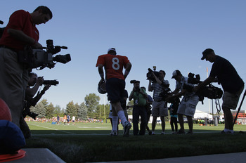 ENGLEWOOD, CO - JULY 28:  Quarterback Kyle Orton #8 of the Denver Broncos takes the field under the scutiny of the media for the first session of training camp at the Paul D. Bowlen Memorial Broncos Centre at Dove Valley on July 28, 2011 in Englewood, Col