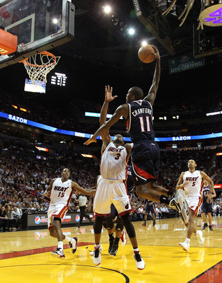 MIAMI, FL - JANUARY 18:  Jamal Crawford #11 of the Atlanta Hawks shoots over Dwyane Wade #3 of the Miami Heat during a game at American Airlines Arena on January 18, 2011 in Miami, Florida. NOTE TO USER: User expressly acknowledges and agrees that, by dow