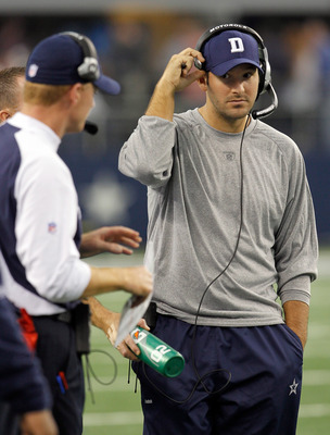ARLINGTON, TX - NOVEMBER 21:  Injured quarterback Tony Romo #9 of the Dallas Cowboys stands on the sidelines with head coach Jason Garrett at Cowboys Stadium on November 21, 2010 in Arlington, Texas.  The Cowboys beat the Detroit Lions 35-19 with backup q