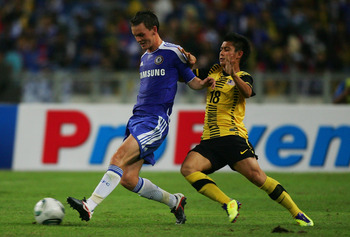KUALA LUMPUR, MALAYSIA - JULY 21: Joshua McEachran (L) of Chelsea battles with Wan Zaharul of Malaysia during the pre-season friendly match between Malaysia and Chelsea at Bukit Jalil National Stadium on July 21, 2011 in Kuala Lumpur, Malaysia.  (Photo by