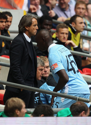 LONDON, ENGLAND - AUGUST 07:  Manchester City manager Roberto Mancini looks on as Mario Balotelli walks to the substitute bench during the FA Community Shield match sponsored by McDonald's between Manchester City and Manchester United at Wembley Stadium o