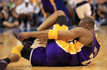 DALLAS, TX - MARCH 12:  Guard Kobe Bryant #24 of the Los Angeles Lakers grabs his foot after suffering an injury during play against the Dallas Mavericks at American Airlines Center on March 12, 2011 in Dallas, Texas.  NOTE TO USER: User expressly acknowl