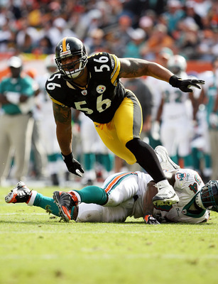 MIAMI - JANUARY 03:  Linebacker LaMarr Woodley #56 of the Pittsburgh Steelers tries to get into the backfield after running over running back Ricky Williams #34 of the Miami Dolphins at Land Shark Stadium on January 3, 2010 in Miami, Florida.  (Photo by D