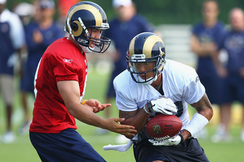 EARTH CITY, MO - JULY 31:  Sam Bradford #8 of the St. Louis Rams hands the ball off to teammate Austin Pettis #83 during training camp at the Russell Training Center on July 31, 2011 in Earth City, Missouri.  (Photo by Dilip Vishwanat/Getty Images)