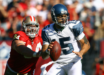 SAN FRANCISCO - OCTOBER 26:  Quarterback Seneca Wallace #15 of the Seattle Seahawks drops back to pass while being pursued by Justin Smith #94 of the San Francisco 49ers in the second quarter at Candlestick Park on October 26, 2008 in San Francisco, Calif