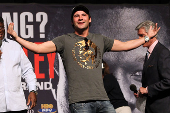 LAS VEGAS - APRIL 30:  Boxer Joe Calzaghe of Wales reacts to the crowd from the stage before the start of the Floyd Mayweather Jr. and Shane Mosley weigh-in at the MGM Grand Garden Arena on April 30, 2010 in Las Vegas, Nevada. Mayweather and Mosley will m