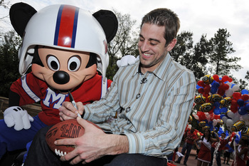 LAKE BUENA VISTA, FL - FEBRUARY 07:  In this handout photo provided by Disney, Super Bowl XLV Most Valuable Player Aaron Rodgers signs a football during a celebratory ride with Mickey Mouse, following the Green Bay Packers' 31-25 victory over the Pittsbur