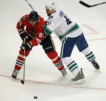 CHICAGO, IL - APRIL 24: Marian Hossa #81 of the Chicago Blackhawks controls the puck under pressure from Andrew Alberts #41 of the Vancouver Canucks in Game Six of the Western Conference Quarterfinals during the 2011 NHL Stanley Cup Playoffs at the United