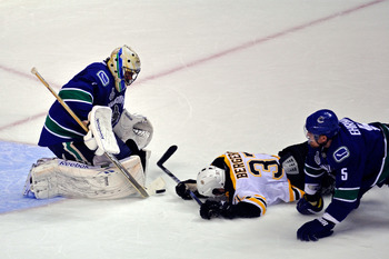VANCOUVER, BC - JUNE 15:  Patrice Bergeron #37 of the Boston Bruins slides on the ice as he scores the 3rd goal in the second period against Roberto Luongo #1 of the Vancouver Canucks during Game Seven of the 2011 NHL Stanley Cup Final at Rogers Arena on