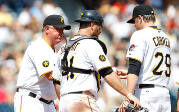 PITTSBURGH - AUGUST 07: Kevin Correia #29 of the Pittsburgh Pirates is pulled by manager Clint Hurdle #13 in front of teammate Ryan Doumit #41 during the game against  the San Diego Padres on August 7, 2011 at PNC Park in Pittsburgh, Pennsylvania.  (Photo