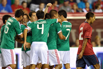 PHILADELPHIA, PA - AUGUST 10: The Mexican team celebrates a goal by Oribe Peralta #19 as Edgar Castillo #2 of the United States walks by at Lincoln Financial Field on August 10, 2011 in Philadelphia, Pennsylvania. (Photo by Drew Hallowell/Getty Images)