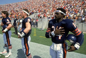 Walter Payton #34 of the Chicago Bears stands for the National Anthem with Jim McMahon #9 before a game.