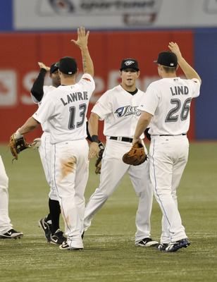 TORONTO, CANADA - AUGUST 10:  Brett Lawrie #13, Colby Rasmus #28 and Adam Lind #26 of the Toronto Blue Jays celebrate the teams win over the Oakland Athletics during MLB game action August 10, 2011 at Rogers Centre in Toronto, Ontario, Canada. (Photo by B
