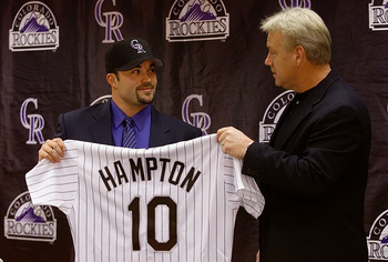 09 Dec 2000:  Pitcher Mike Hampton holds up his Colorado Rockies jersey and dons the team cap with the help of manager Buddy Bell during a press conference at Coors Field in Denver, Colorado.  Hampton, a free agent, was signed away from the New York Mets