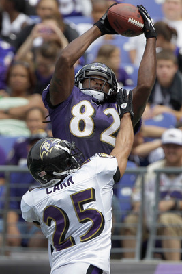 BALTIMORE, MD - AUGUST 06:  Wide receiver Torrey Smith #82 of the Baltimore Ravens catches a pass in front of defensive back Chris Carr #25 during training camp at M&T Bank Stadium on August 6, 2011 in Baltimore, Maryland.  (Photo by Rob Carr/Getty Images