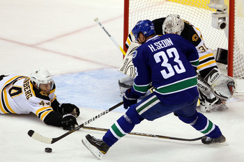 VANCOUVER, BC - JUNE 15:  Dennis Seidenberg #44 of the Boston Bruins falls on the ice defend against Henrik Sedin #33 of the Vancouver Canucks during Game Seven of the 2011 NHL Stanley Cup Final at Rogers Arena on June 15, 2011 in Vancouver, British Colum