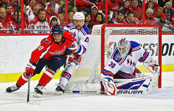 WASHINGTON , DC - APRIL 23:  Matt Bradley #10 of the Washington Capitals attempts a wrap around shot on goal against Bryan McCabe #28 and Henrik Lundqvist #30 of the New York Rangers in Game Five of the Eastern Conference Quarterfinals during the 2011 NHL