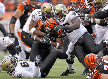 CINCINNATI, OH - DECEMBER 05:  Jonathan Vilma  #51 and Sedrick Ellis #98 of the New Orleans Saints tackle Cedric Benson #32 of the Cincinnati Bengals during the NFL game at Paul Brown Stadium on December 5, 2010 in Cincinnati, Ohio.  The Saints won 34-30.