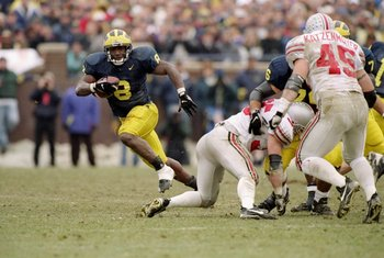 22 Nov 1997:  Tailback Chris Howard of the Michigan Wolverines (left) runs with the ball as linebacker Andy Katzenmoyer of the Ohio State Buckeyes (right) runs toward him during a game at Michigan Stadium in Ann Arbor, Michigan.  Michigan won the game 20-