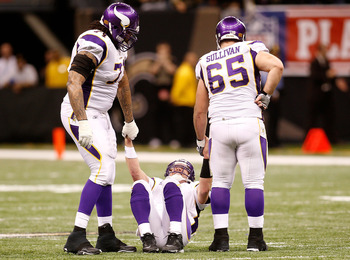 NEW ORLEANS - JANUARY 24:  Brett Favre #4 of  the Minnesota Vikings is helped up by teammates Phil Loadholt #71 and John Sullivan #65 after he took a hard hit in the second half against the New Orleans Saints during the NFC Championship Game at the Louisi