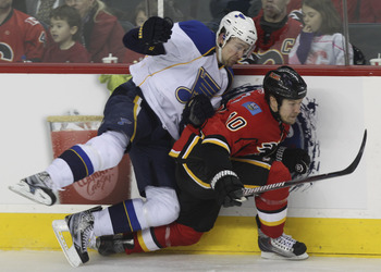 CALGARY, AB - FEBRUARY 27: Niklas Hagman #10 of the Calgary Flames ducks unders a check from Patrik Berglund #21 of the St. Louis Blues in the third period of NHL action on February 27, 2011 at the Scotiabank Saddledome in Calgary, Alberta, Canada. (Photo