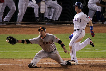 ARLINGTON, TX - OCTOBER 31:  Michael Young #10 of the Texas Rangers is safe at first base as Travis Ishikawa #10 of the San Francisco Giants reaches for a throw from teammate Freddy Sanchez #21 (not pictured) in the fourth inning in Game Four of the 2010