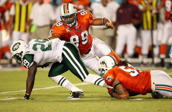 MIAMI - OCTOBER 12:  Running back Leon Washington #29 of the New York Jets tries to slip a tackle attempt by linebackers Channing Crowder #52 and Jason Taylor #99 of the Miami Dolphins at Land Shark Stadium on October 12, 2009 in Miami, Florida.  (Photo b