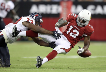 GLENDALE, AZ - AUGUST 14:  Wide receiver Andre Roberts #12 of the Arizona Cardinals loses the ball as he is hit by Troy Nolan #33 of the Houston Texans during preseason NFL game at the University of Phoenix Stadium on August 14, 2010 in Glendale, Arizona.