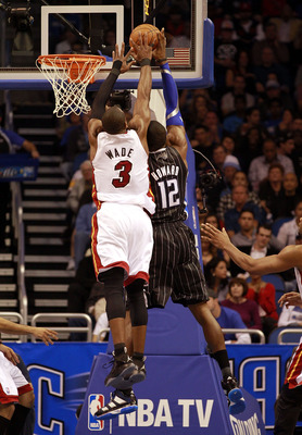 ORLANDO, FL - FEBRUARY 03:  Guard Dwyane Wade #3 of the Miami Heat blocks the shot of center Dwight Howard #12 of the Orlando Magic at Amway Arena on February 3, 2011 in Orlando, Florida. NOTE TO USER: User expressly acknowledges and agrees that, by downl