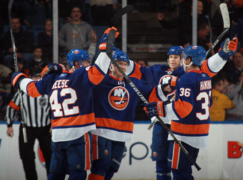 UNIONDALE, NY - MARCH 31: (L-R) Dylan Reese #42, Blake Comeau #57, Matt Martin #17 and Travis Hamonic #36 of the New York Islanders celebrate a goal at 14:00 of the third period by Trevor Gillies #14 of the New York Islanders against the New York Rangers