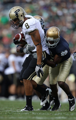 SOUTH BEND, IN - SEPTEMBER 04: Keith Smith #8 of the Purdue Boilermakers is stopped by Darrin Walls #2 (R) and Jamoris Slaughter #26 of the Notre Dame Fighting Irish at Notre Dame Stadium on September 4, 2010 in South Bend, Indiana. Notre Dame defeated Pu