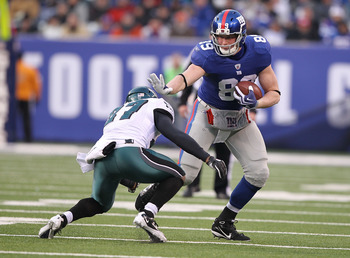 EAST RUTHERFORD, NJ - DECEMBER 19:  Kevin Boss #89 of the New York Giants stiff arms Quintin Mikell #27 of the Philadelphia Eagles during their game on December 19, 2010 at The New Meadowlands Stadium in East Rutherford, New Jersey.  (Photo by Al Bello/Ge