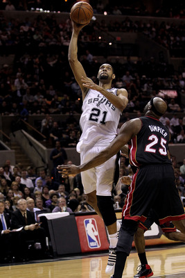 SAN ANTONIO, TX - MARCH 04:  Forward Tim Duncan #21 of the San Antonio Spurs takes a shot against Erick Dampier #25 of the Miami Heat at AT&T Center on March 4, 2011 in San Antonio, Texas.   NOTE TO USER: User expressly acknowledges and agrees that, by do
