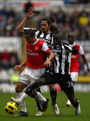 NEWCASTLE UPON TYNE, ENGLAND - FEBRUARY 05:  Theo Walcott of Arsenal holds off Jonas Gutierrez and Cheik Tiote of Newcastle during the Barclays Premier League match between Newcastle United and Arsenal at St James' Park on February 5, 2011 in Newcastle up