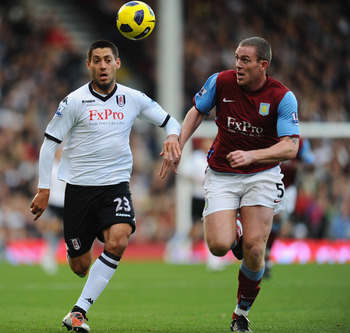 LONDON, ENGLAND - NOVEMBER 06:  Richard Dunn of Aston Villa is challenged by Clint Dempsey of Fulham during the Barclays Premier League match between Fulham and Aston Villa at Craven Cottage on November 6, 2010 in London, England.  (Photo by Mike Hewitt/G