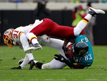 JACKSONVILLE, FL - DECEMBER 26:  Jason Hil #83 of the Jacksonville Jaguars is tackled by Phillip Buchanon #31 of the Washington Redskins during the game at EverBank Field on December 26, 2010 in Jacksonville, Florida.  (Photo by Sam Greenwood/Getty Images