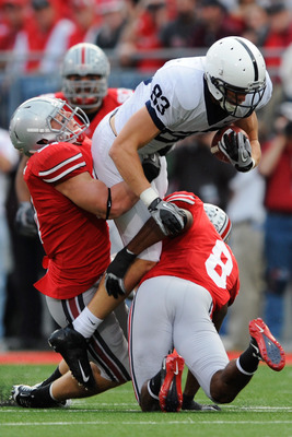 COLUMBUS, OH - NOVEMBER 13:  Brett Brackett #83 of the Penn State Nittany Lions is tackled by Ross Homan #51 of the Ohio State Buckeyes and Aaron Gant #8 of the Ohio State Buckeyes after making a pass reception at Ohio Stadium on November 13, 2010 in Colu