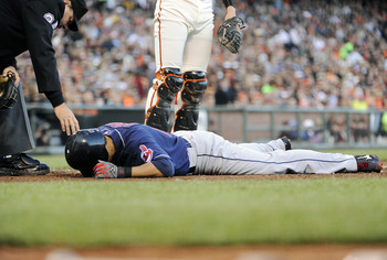 SAN FRANCISCO, CA - JUNE 24: Shin-soo Choo #17 of the Cleveland Indians lies on the ground after being hit in the hand by a pitch from Jonathan Sanchez #57 of the San Francisco Giants in the fourth inning during a MLB baseball game at AT&T Park June 24, 2