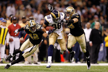 NEW ORLEANS, LA - DECEMBER 12: Keith Toston #38 of the St. Louis Rams is tackled by Darren Sharper #42 and Scott Shanle #58 of the New Orleans Saints at the Louisiana Superdome on December 12, 2010 in New Orleans, Louisiana. The Saints defeated the Rams 3